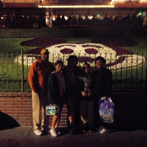 Preteen Maya Purcell's family in front of mickey floral arrangment