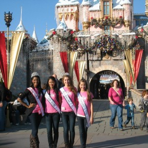 Jr. Teen Team Service Members, Nadgeena Jerome, Tiffany Luk, and Taylor Longbrake join Team Ambition Member Lauren Schwartzberg in front of the Christmas Decorated Disney Castle.