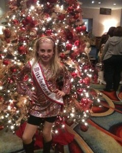 Miss Indiana striking a pose with the beautiful Christmas Tree