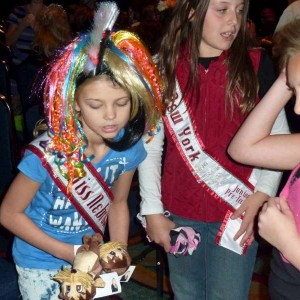 Miss Nebraska giving otters to NAM friends and sister queens at Crazy Hair Day