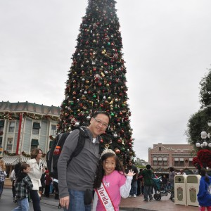 Miss Florida posing with her dad in front of the Christmas Tree