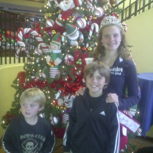 Miss Massachusetts preteen with her brothers in front of Christmas decorations