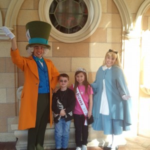 Amber Cochran and her brother posing with The Mad Hatter and Alice