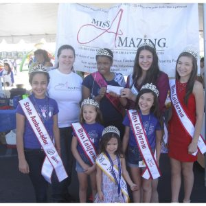 National American Miss California Queen's donate a check to the Miss Amazing Pageant Director after hosting a Talent Showcase for Down Syndrome Awareness Month