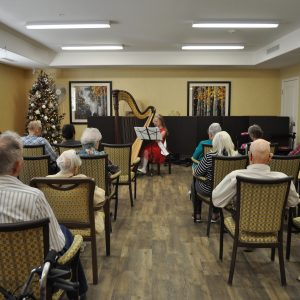 Megan playing hymns and Christmas carols at a retirement home.